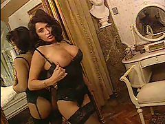 Erica Bella on a bed in black stockings